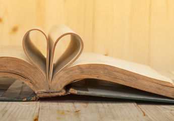 open old book rolled in heart shape