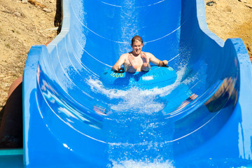Man having fun, sliding at water park