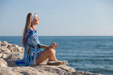 Happy young woman meditating at seacoast