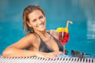 Beautiful woman in black bikini relaxing in the swimming pool