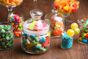 Colorful candies in jars on table on wooden background