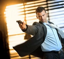 Determined action hero wearing suit holding gun
