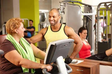 Fat woman and personal trainer in gym