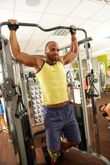 Athletic man in gym doing pull-ups