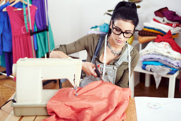 Young female fashion designer working on sewing machine