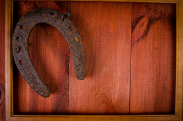 Horseshoe on woody table in picture frame