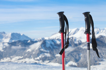 skiing in mountains, close up of two ski poles