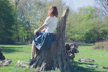 Woman sitting on a tree trunk in the forest
