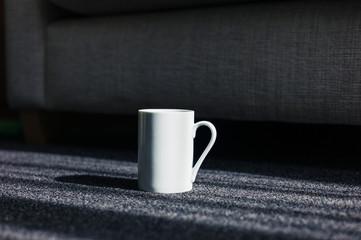 White mug on carpet at home