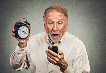 surprised business man with alarm clock looking at smart phone