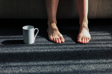Mug next to feet of woman at home