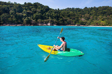 young caucasian man on kayak near paradise island in turquoise water