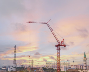 Red crane on construction site in the twilight sky