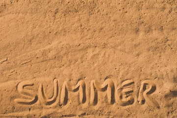 Summer written in the sand on the beach. Vacation background