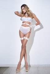 Girl in erotic white lingerie posing against a white wall
