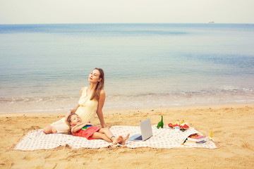 Mother and daughter relax near the sea