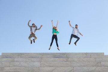 Three friends jump on top of a staircase