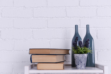 Interior design with plant, glass bottles and stack of books