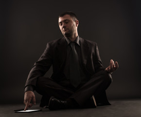 Portrait of impatient businessman looking at digital tablet while meditate isolated on black background.