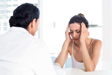 Woman grimacing in front of her doctor