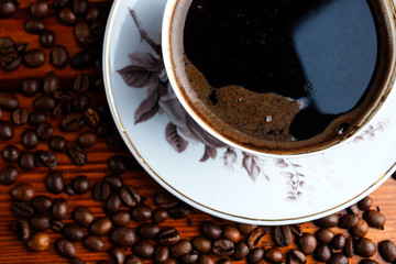 Coffee beans and cup of coffee on wooden table