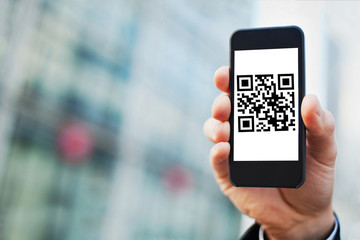 hand holding smartphone with QR code on the screen