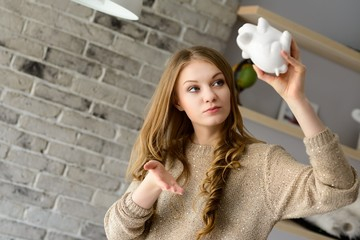 Woman trying to find more money in the piggy bank