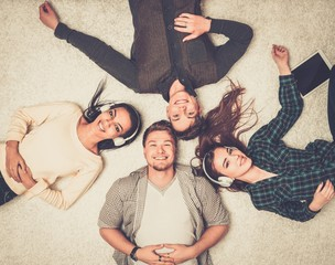 Happy multiracial friends relaxing on a carpet with gadgets