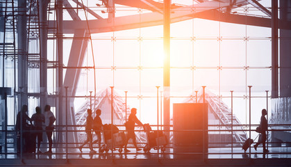 Fotobehang Luchthaven commuters walking in modern airport, back light