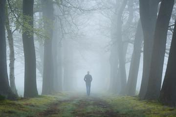 Keuken foto achterwand Grijze traf. Man walking in a mysterious lane on a foggy and dark morning.