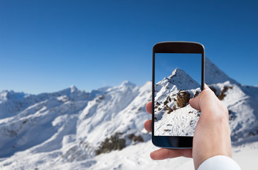 Person Photographing Snowy Mountain Landscape