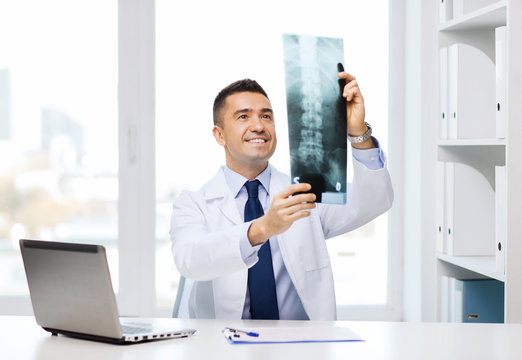 smiling male doctor in white coat looking at x-ray