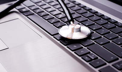 Stethoscope resting on a computer keyboard - concept for online