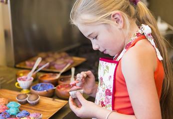 Caucasian girl making cupcakes