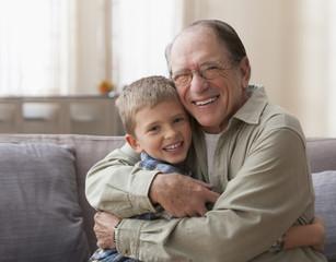 Older Caucasian man hugging grandson on sofa