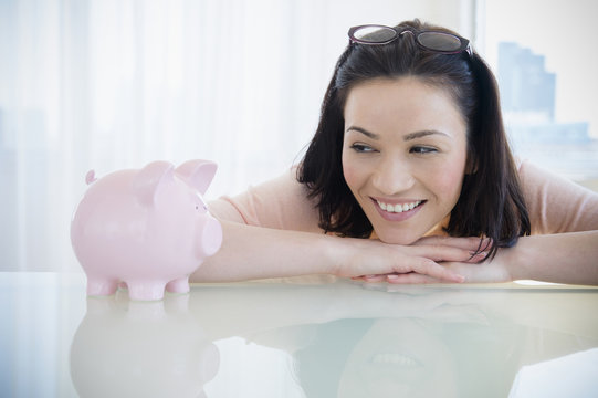 Caucasian woman examining piggy bank