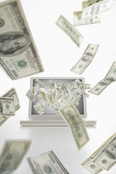 Dollar bills flying from laptop computer