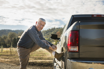 Older Caucasian man tying his shoe on truck wheel