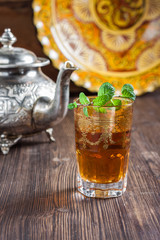 Moroccan tea with mint, iron kettle and traditional dish