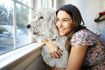 Caucasian woman hugging dog at window