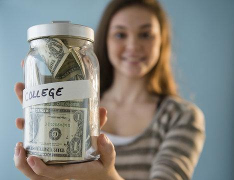 Hispanic girl holding ,'college' savings jar