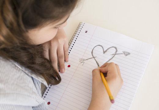 Hispanic girl doodling heart and arrow