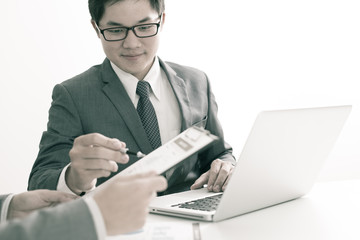 Two businessmen looking at report and having a discussion in off