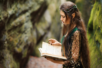 Elf woman reading a book in the mountains, magic tale