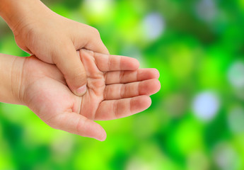 Close up hand pain with blurred abstract green background