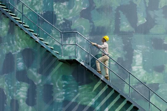 Hispanic worker climbing water tower