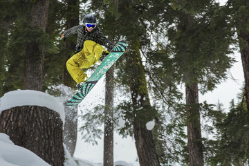 Mixed race snowboarder jumping on snowy slope