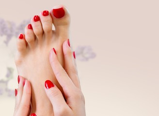 Spa. Closeup photo of a female feet with beautiful red pedicure
