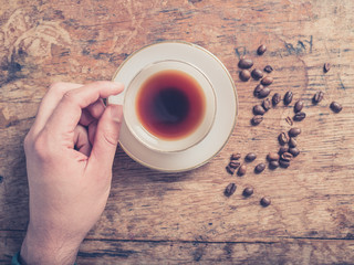 Male hand and coffee with beans on wooden table