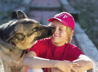 Dog licking Caucasian boy's face